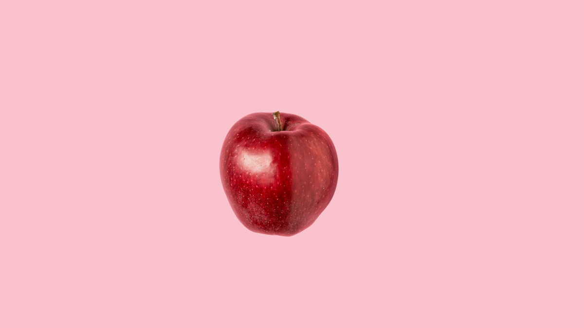 isolated shiny red apple in pink background