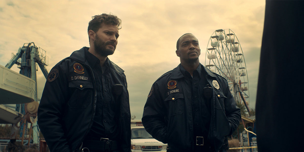 two paramedics, Jamie Dornan and Anthony Mackie, stand beside each other in a carnival. There are rides behind them. A ferris wheel is behind Anthony Mackie.