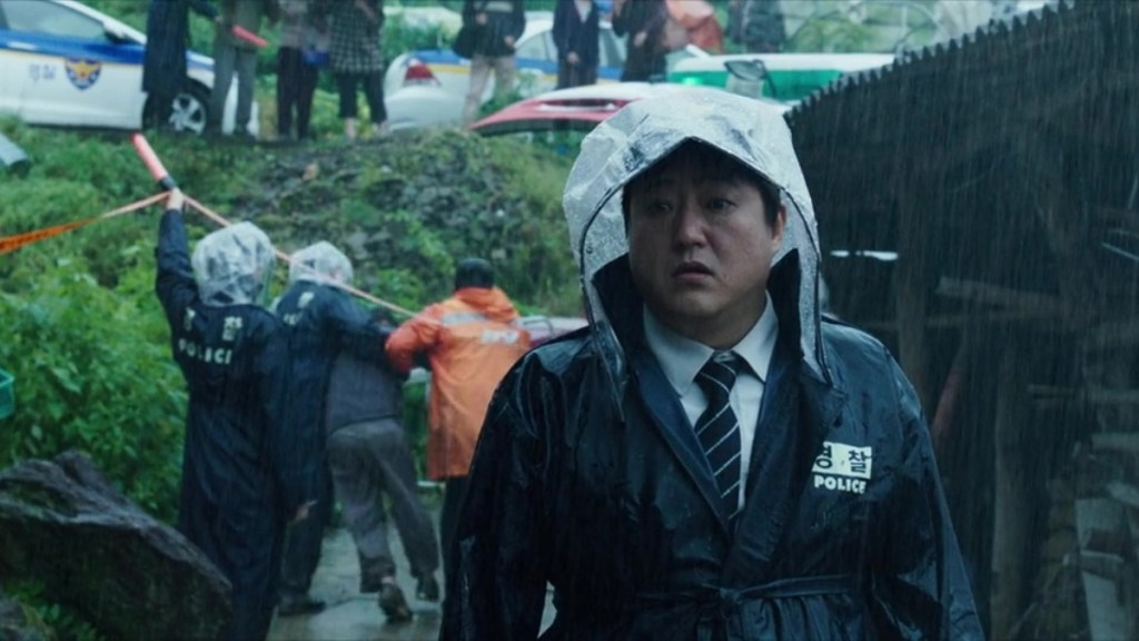 The Wailing - Jong-Goo glares at a crime scene. He's wearing a raincoat.